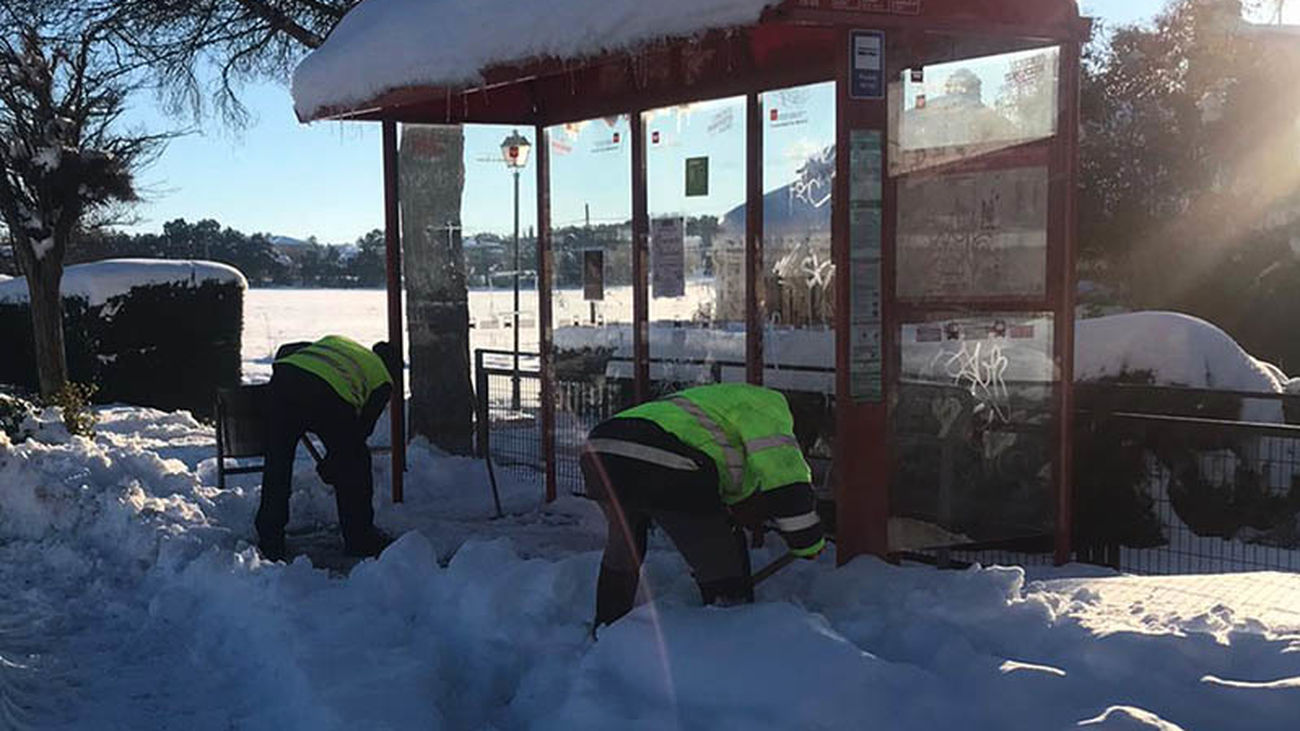 Trabajadores municipales despejan de nieve una marquesina en Nuevo Baztán
