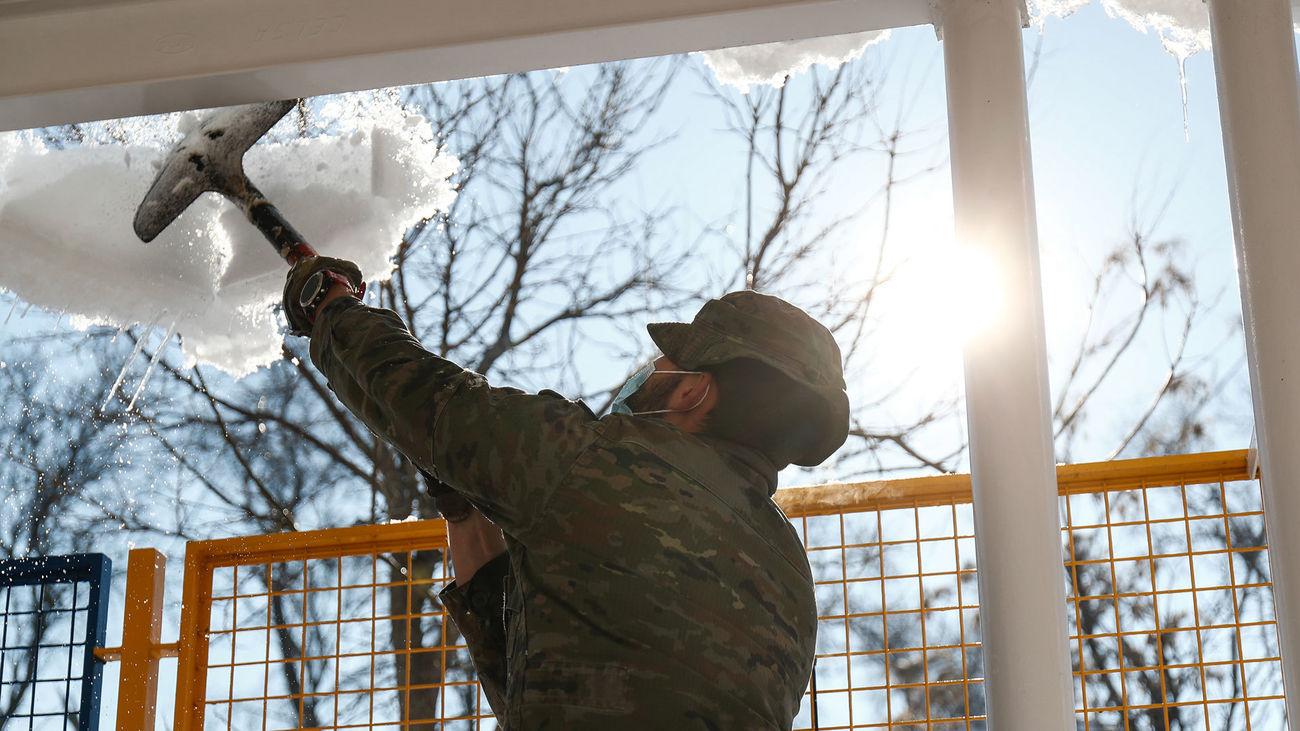 Un militar de la UME colabora en la retirada de nieve y hielo en las inmediaciones del colegio Fuente de la Villa