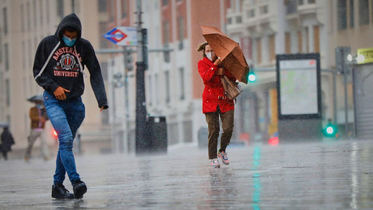 Transeúntes caminan por el centro de Madrid con lluvias y viento