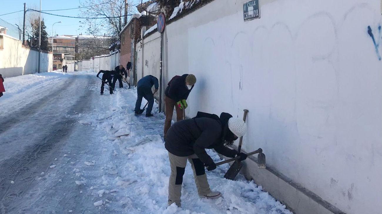 Vecinos retiran nieve para abrir un paso hacia el centro de salud de Aguacate, Carabanchel