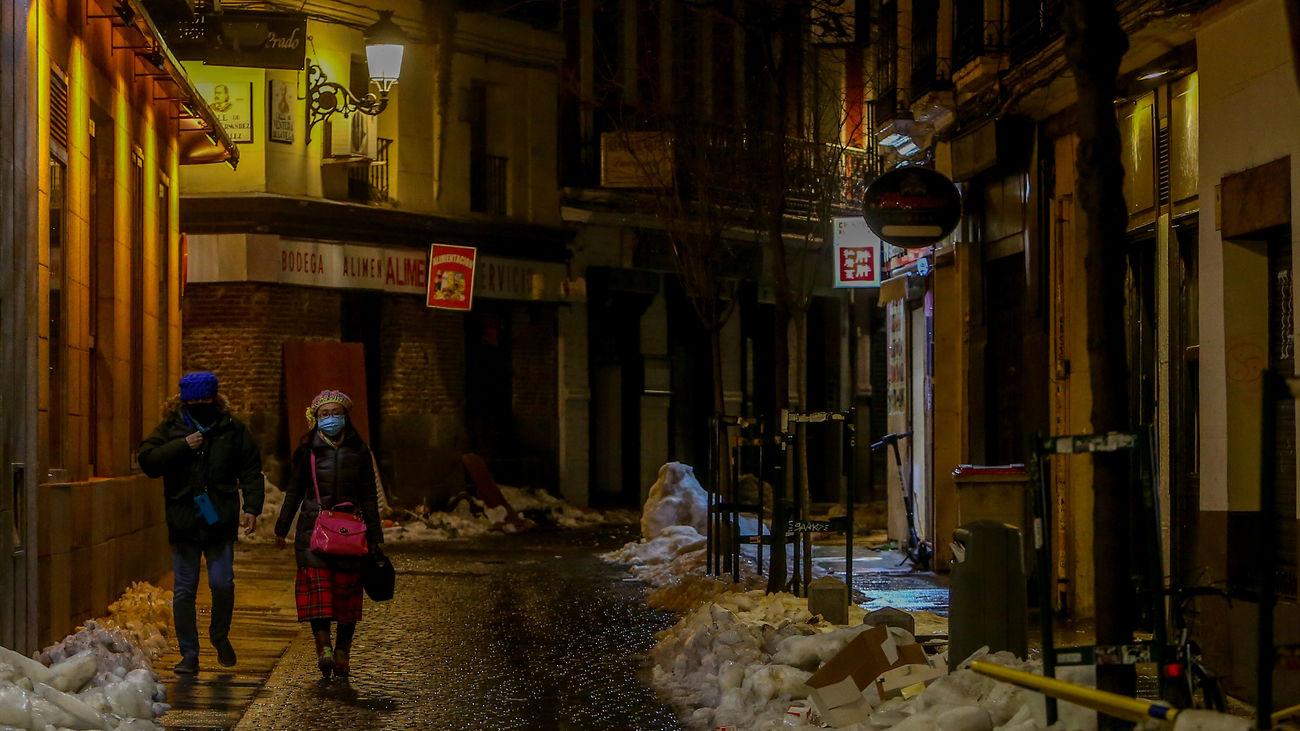 Dos personas pasean de noche por una calle de Madrid