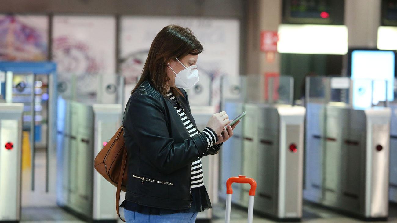 Una viajera con mascarilla consulta su móvil en la estación de Atocha