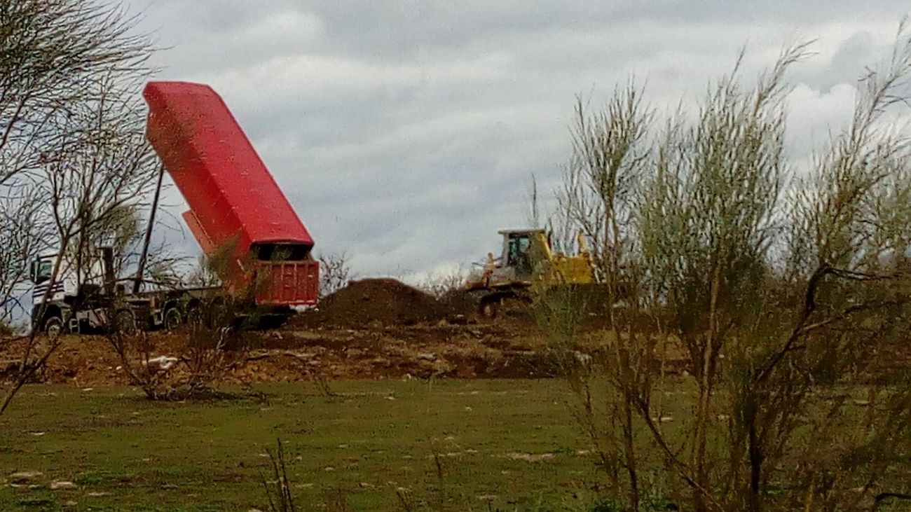 Un camión vuelca su carga junto a una escombrera, cerca de la A-5