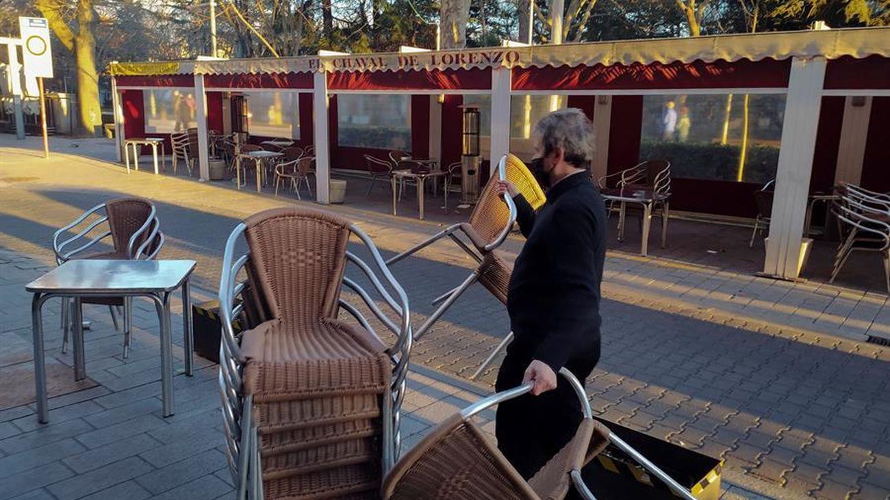 Un hostelero recoge la terraza de su local