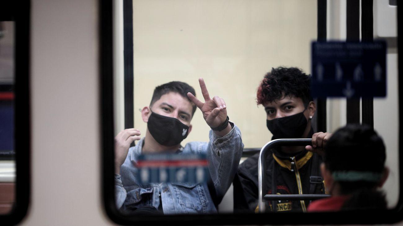 Dos jóvenes a bordo de un vagón de Metro de Madrid