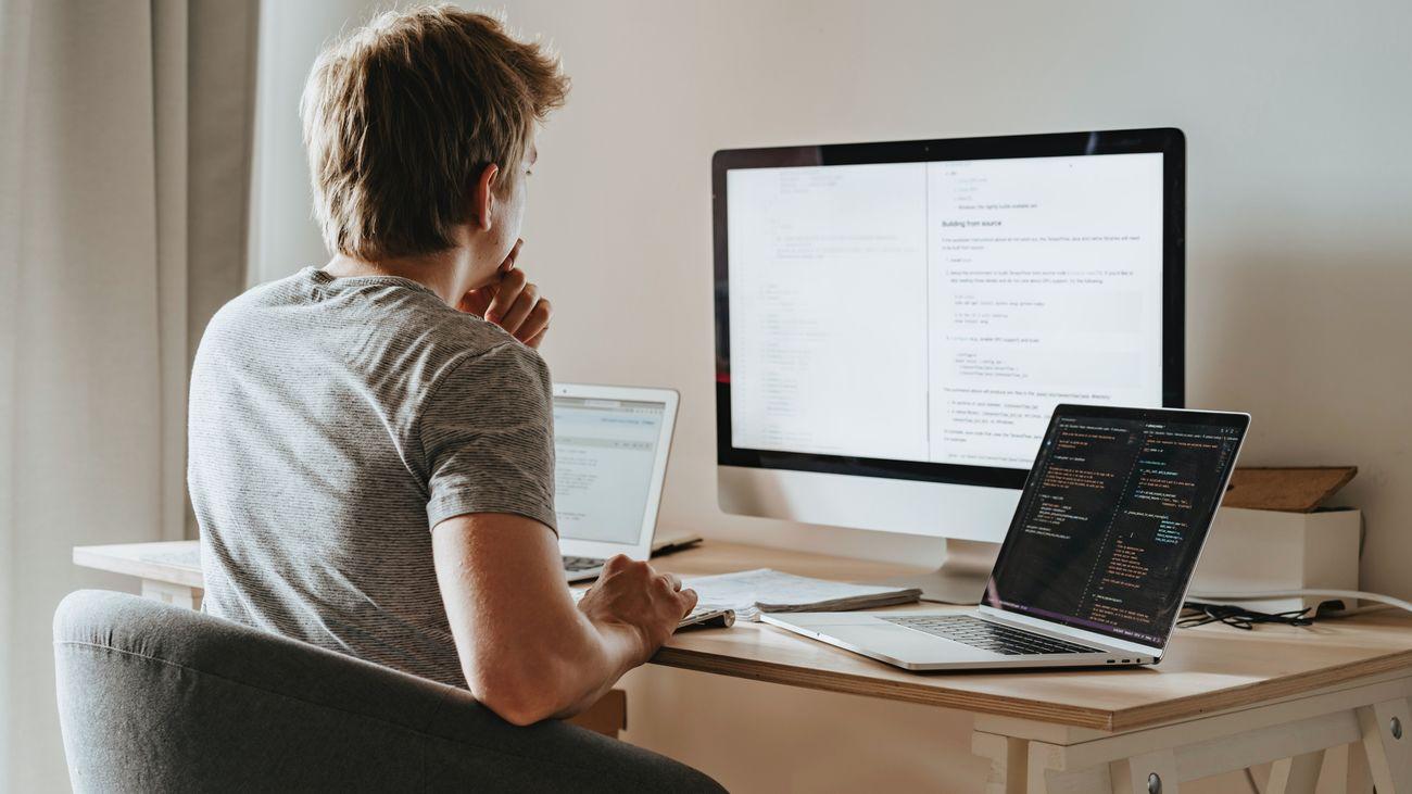 Persona teletrabajando en su casa con varios ordenadores