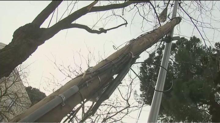 Denuncian el peligro de un poste de la luz que lleva caído sobre una farola un mes en Arturo Soria