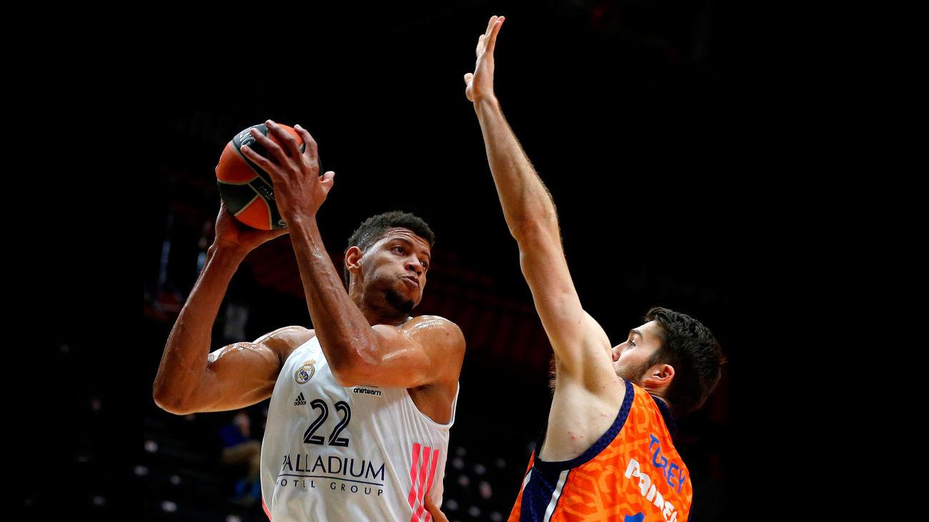 El pívot caboverdiano del Real Madrid Walter Tavares intenta superar al pívot estadounidense del Valencia Basket, Mike Tobey