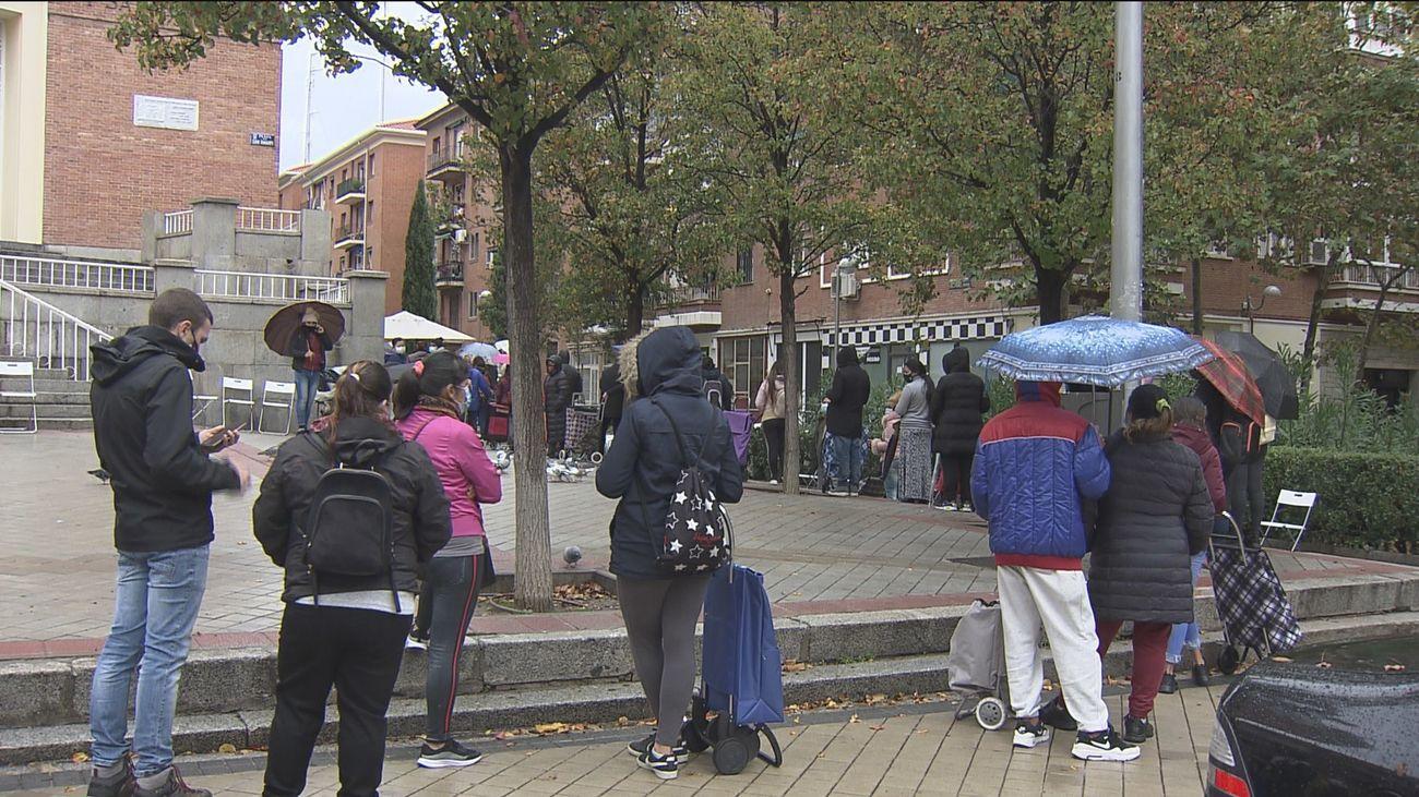 Un grupo de personas espera para poder recibir una donación de alimentos en Madrid