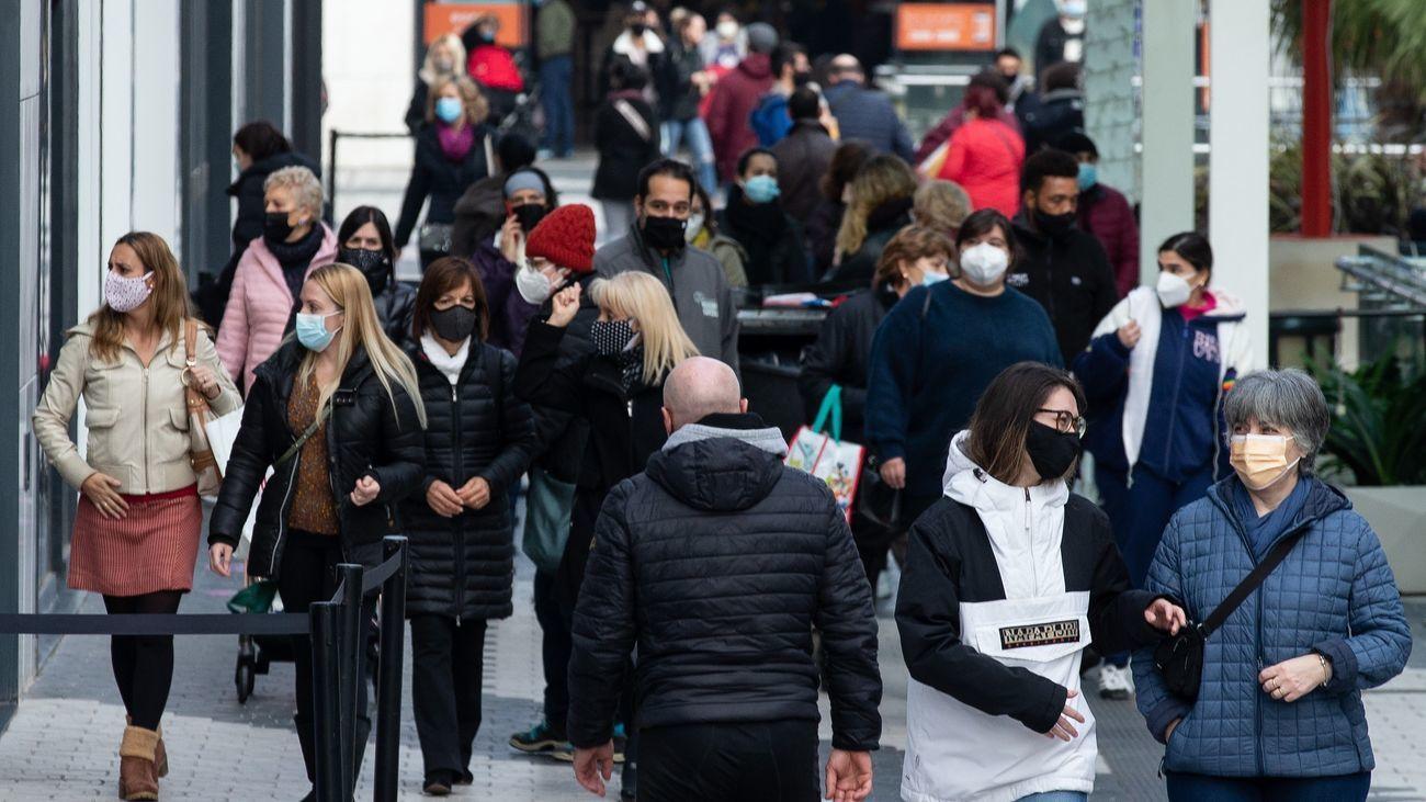 Personas transitan por una calle comercial