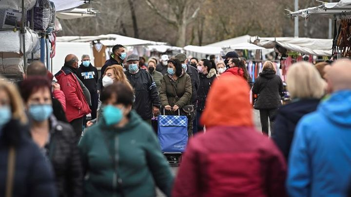 Varias personas con mascarilla en un mercadillo madrileño