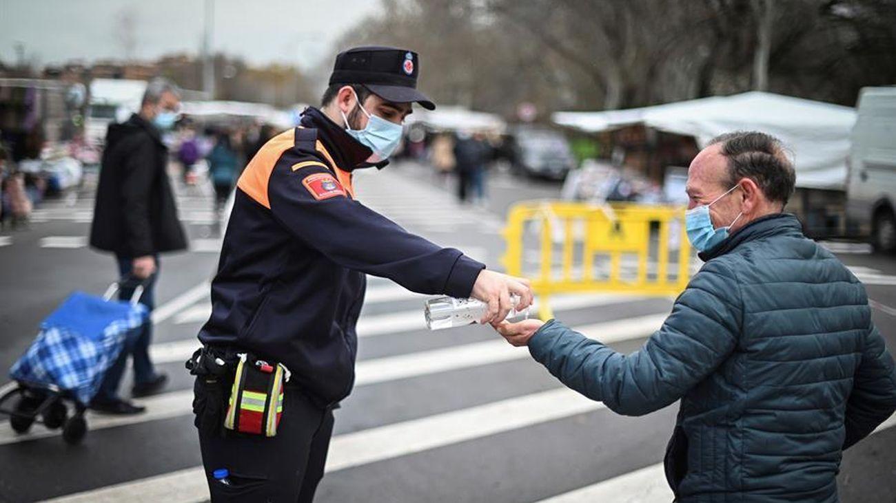 Un vigilante de seguridad ofrece gel hidroalcohólico a un hombre a la entrada de un mercadillo en Madrid