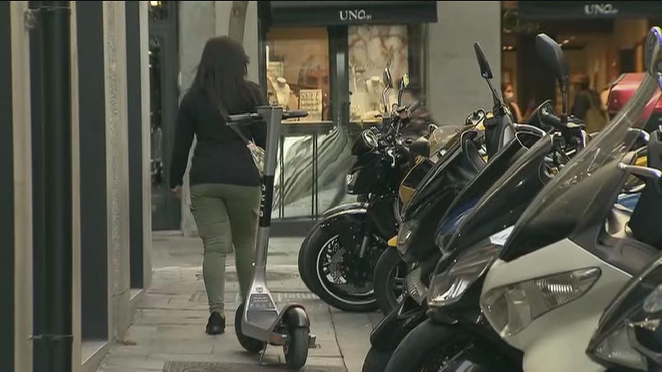 Patinetes y motos aparcados en la acera en Madrid