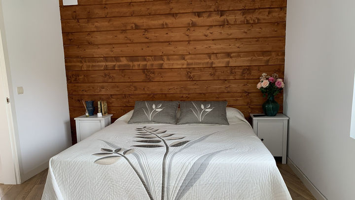El cabecero de la cama es una pared forrada de madera.