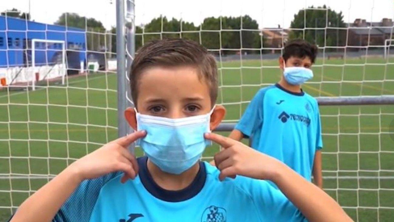 Un niño muestra su mascarilla en una instalación deportiva