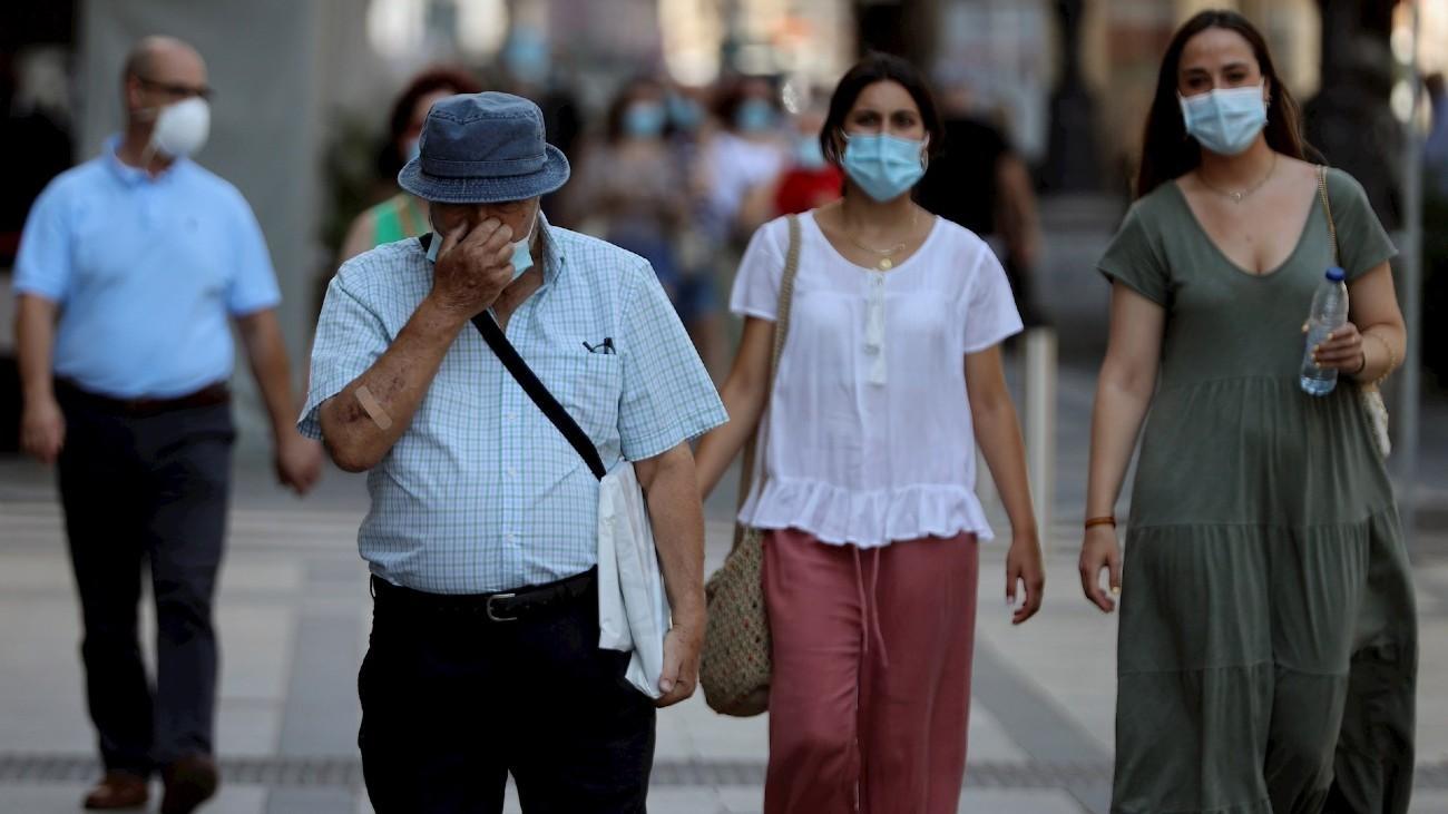 Personas con mascarillas caminan por la calle