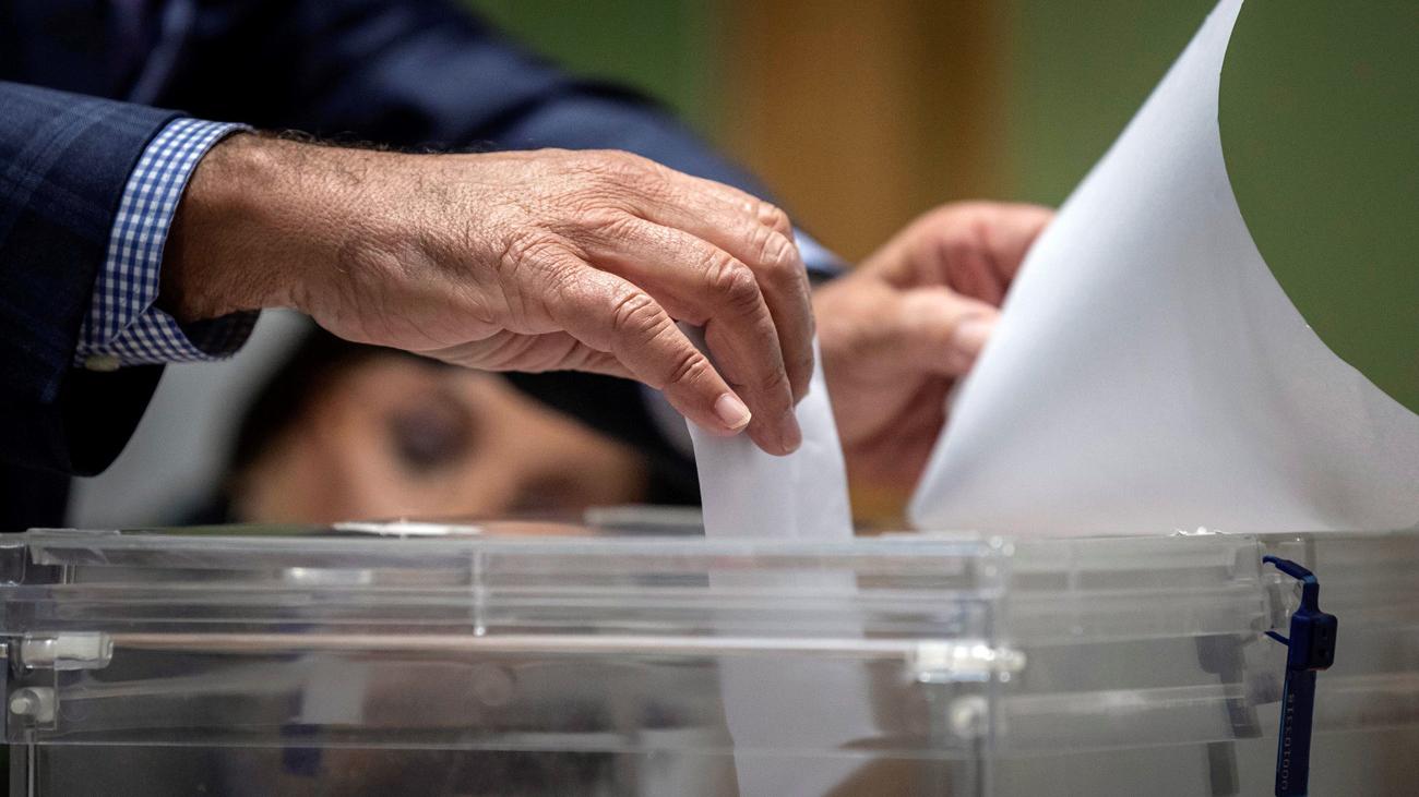 Un miembro de una mesa electoral introduce el voto en la urna