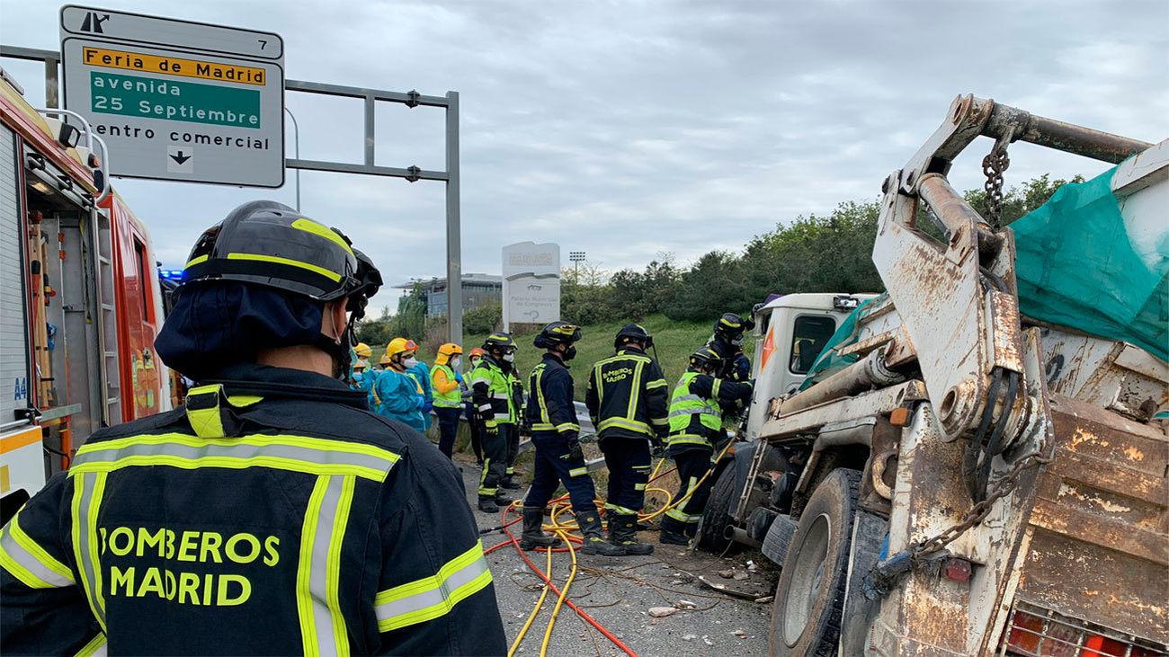 Los bomberos tratan de rescatar al camionero atrapado tras un accidente en la M-40