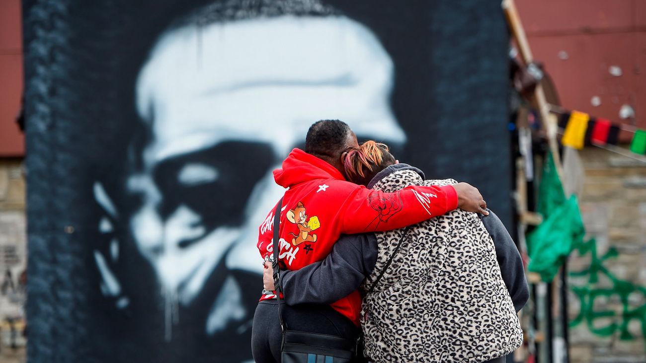 Una pareja se abraza frente al retrato de George Floyd