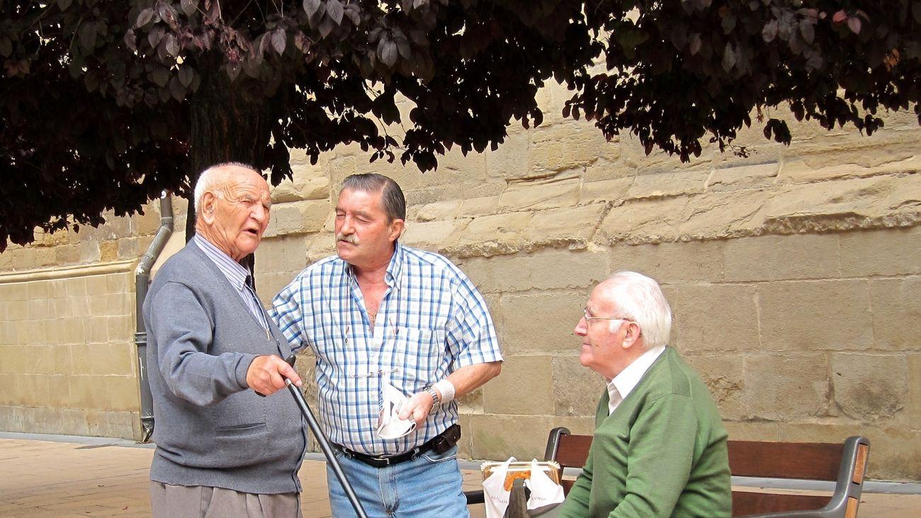 Personas mayores charlan junto a un banco