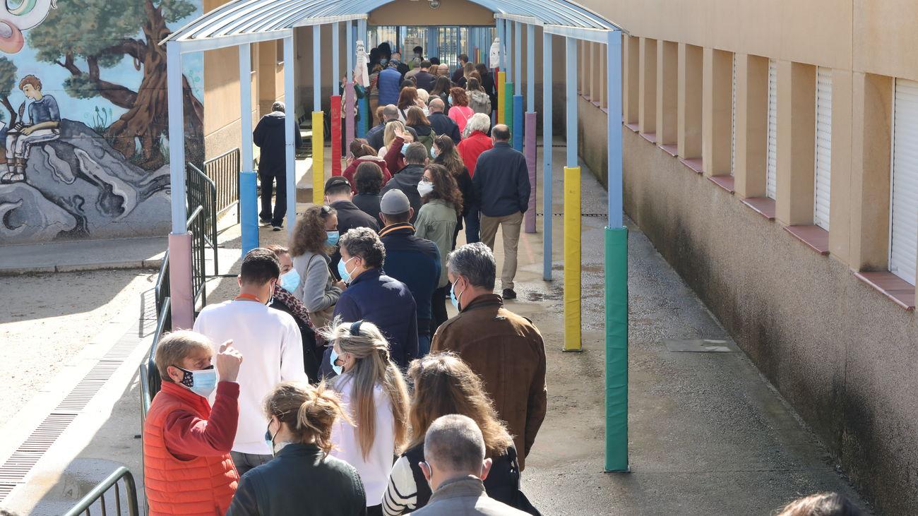 Fila de personas esperando para acceder al colegio electoral y poder votar