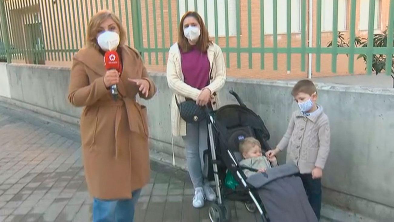 Una madre acude con sus dos hijos pequeños a la mesa electoral