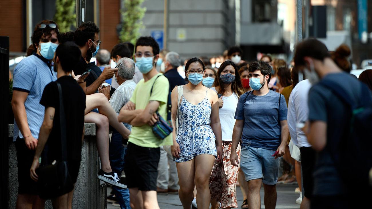 Varias personas caminan con mascarilla por una calle del centro de Madrid
