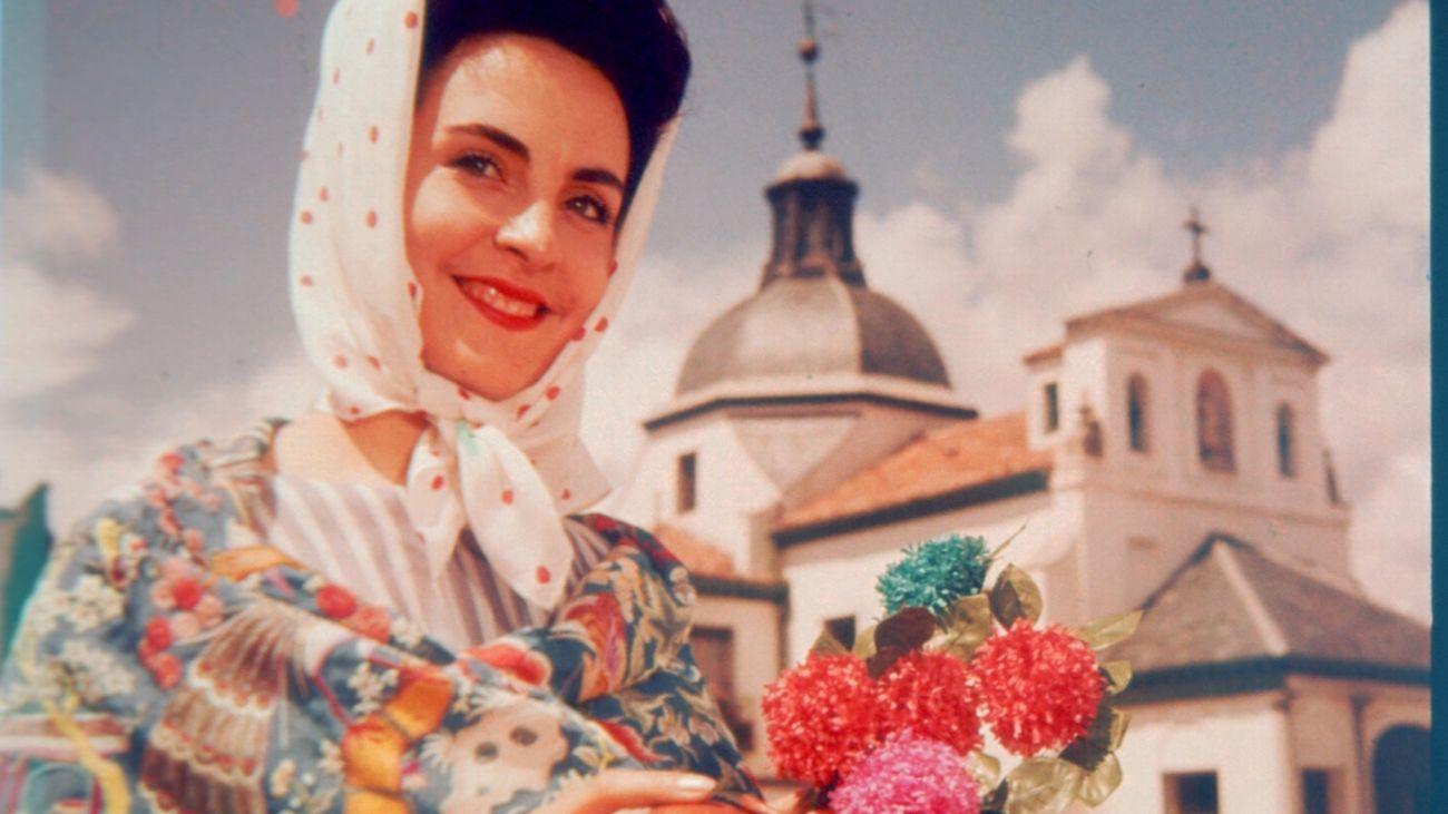 Una chulapa con botijo posa frente a la Ermita de San Isidro