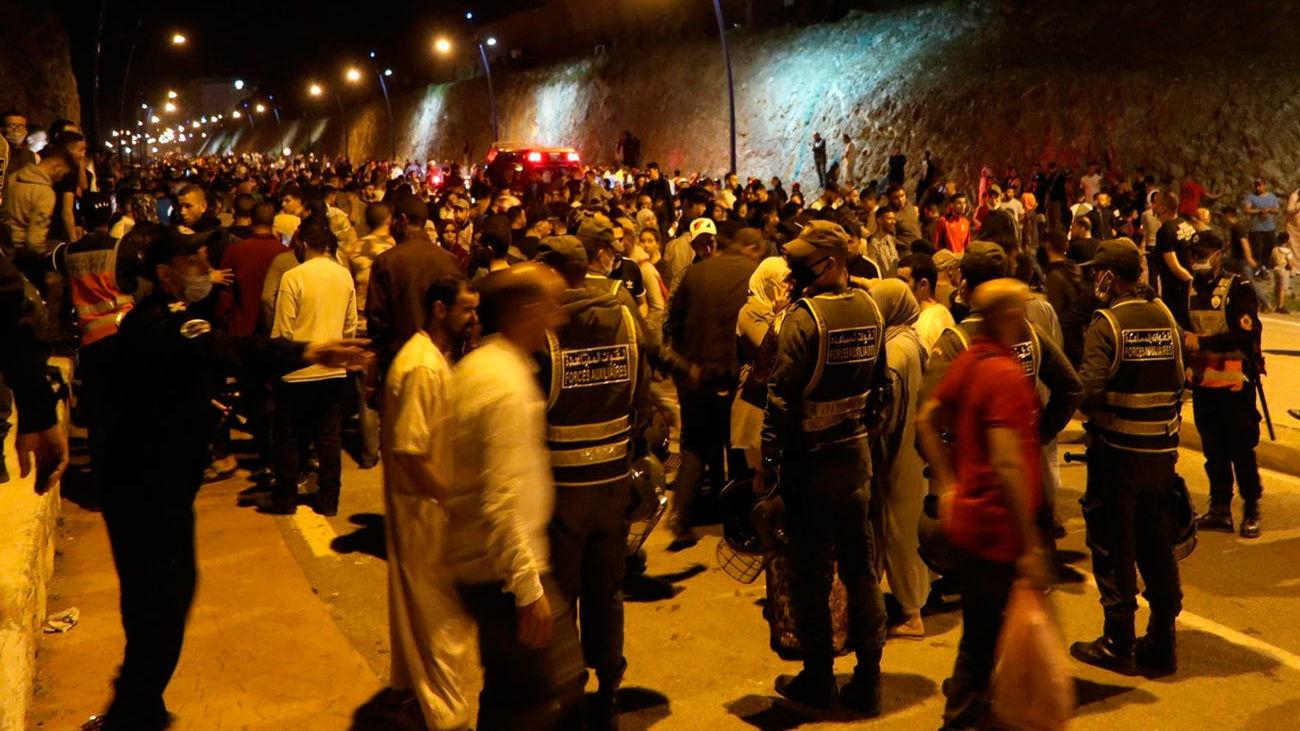 Jóvenes marroquíes esperan el momento de cruzar la frontera, por tierra o agua, este lunes en la localidad de Castillejos.