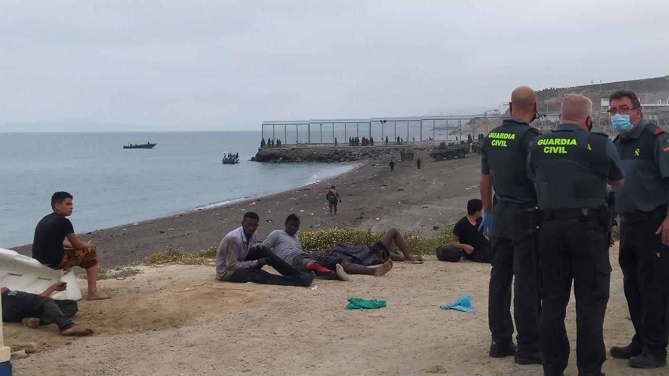 Miembros de la Guardia Civil conversan junto a un grupo de inmigrantes que han cruzado la frontera a nado