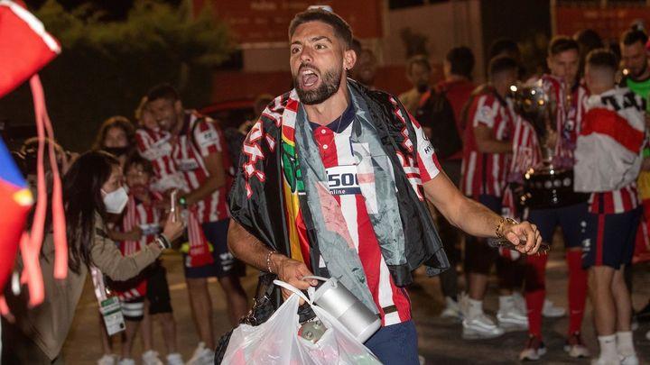 El jugador belga del Atlético de Madrid Yannick Carrasco celebra con la afición a su llegada esta noche a la Ciudad deportiva Wanda