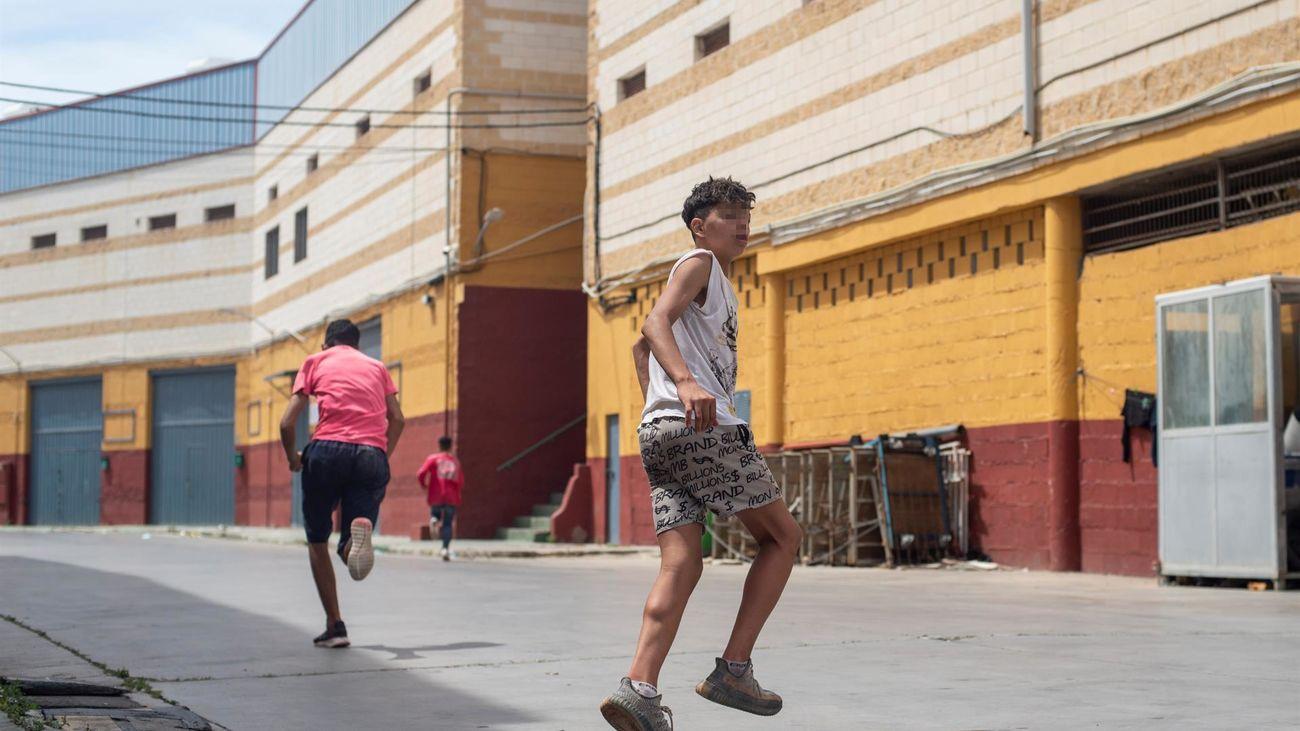 res migrantes se escapan de la nave del polígono industrial cercano a la playa de El Tarajal en donde permanecen gran parte de los menores migrantes llegados a Ceuta