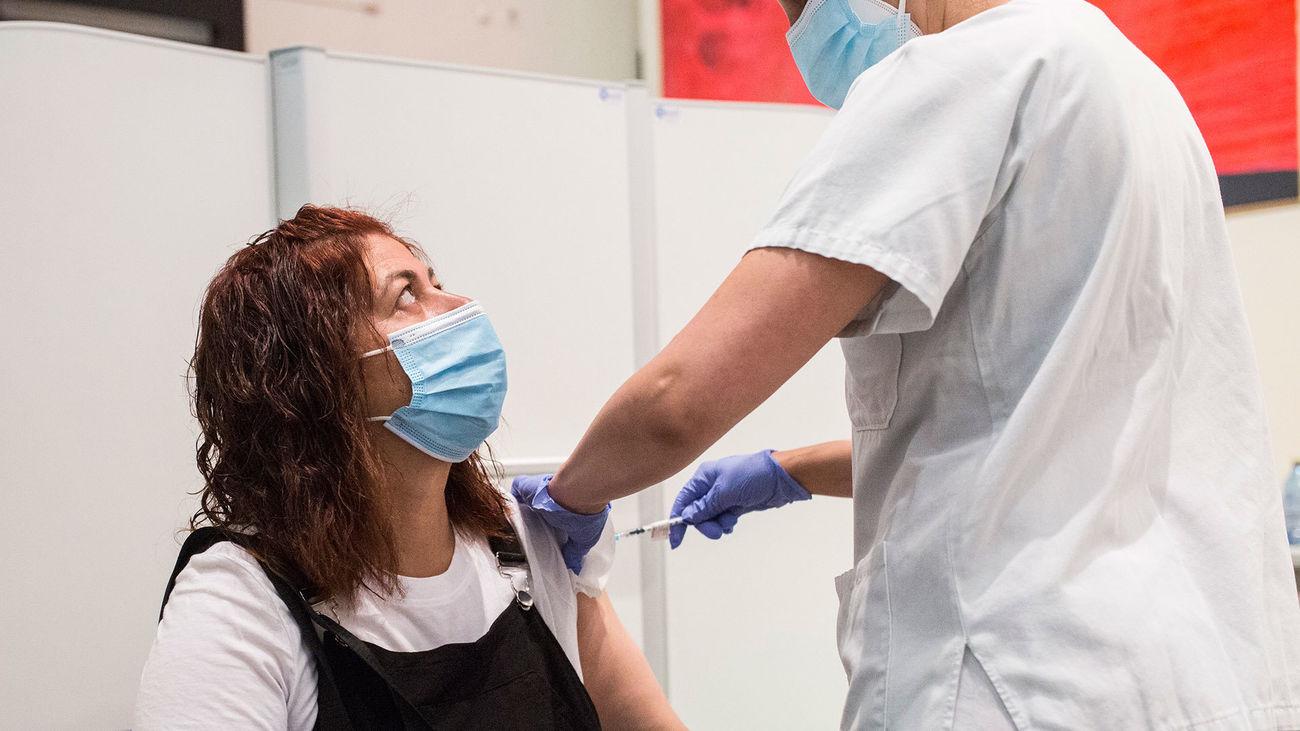 Una sanitaria administra la primera dosis de la vacuna de Pfizer a una mujer, en el Hospital Universitario de Getafe