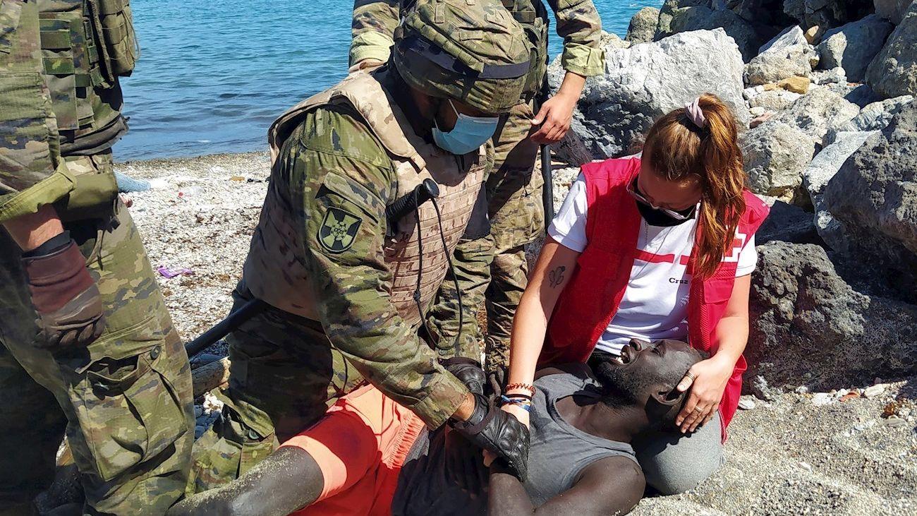La voluntaria de Cruz Roja Luna Reyes y miembros del Ejército de Tierra atienden a un migrante llegada a Ceuta