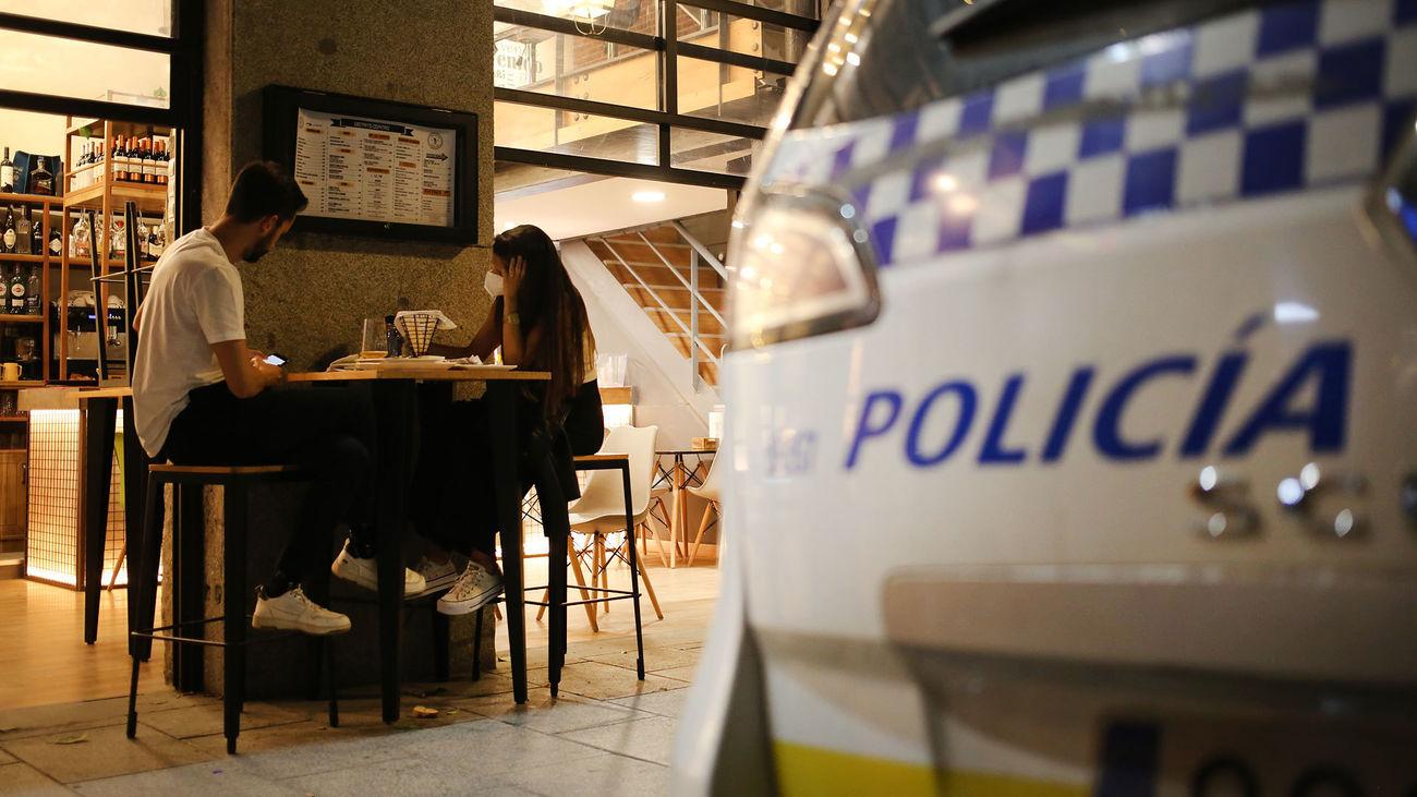 Una pareja cena en una terraza de Madrid junto a un coche de la Policía Municipal