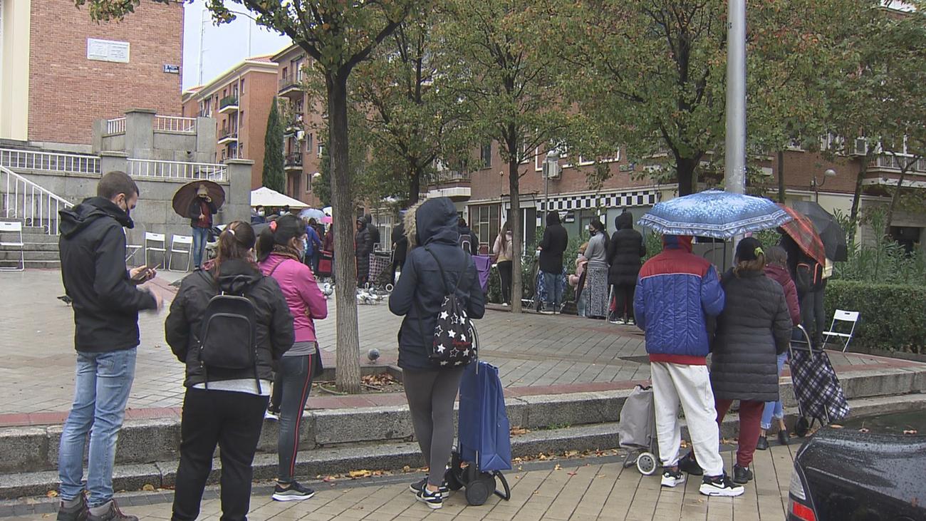 Numerosas personas aguardan en una cola para recoger alimentos