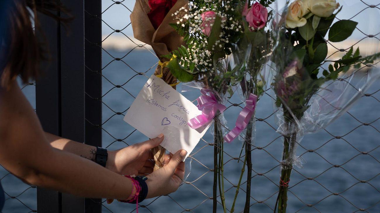 Una mujer coloca un ramo de flores en el puerto de Santa Cruz de Tenerife, frente a cuya costa aparUna mujer coloca un ramo de flores en el puerto de Santa Cruz de Tenerife, frente a cuya costa aparecía ayer el cuerpo de una de las niñas desaparecidas.ecía ayer el cuerpo de una de las niñas desaparecidas.