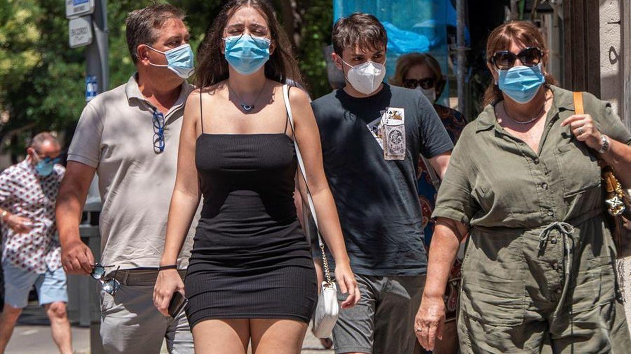 Varias personas caminan por la calle con mascarilla