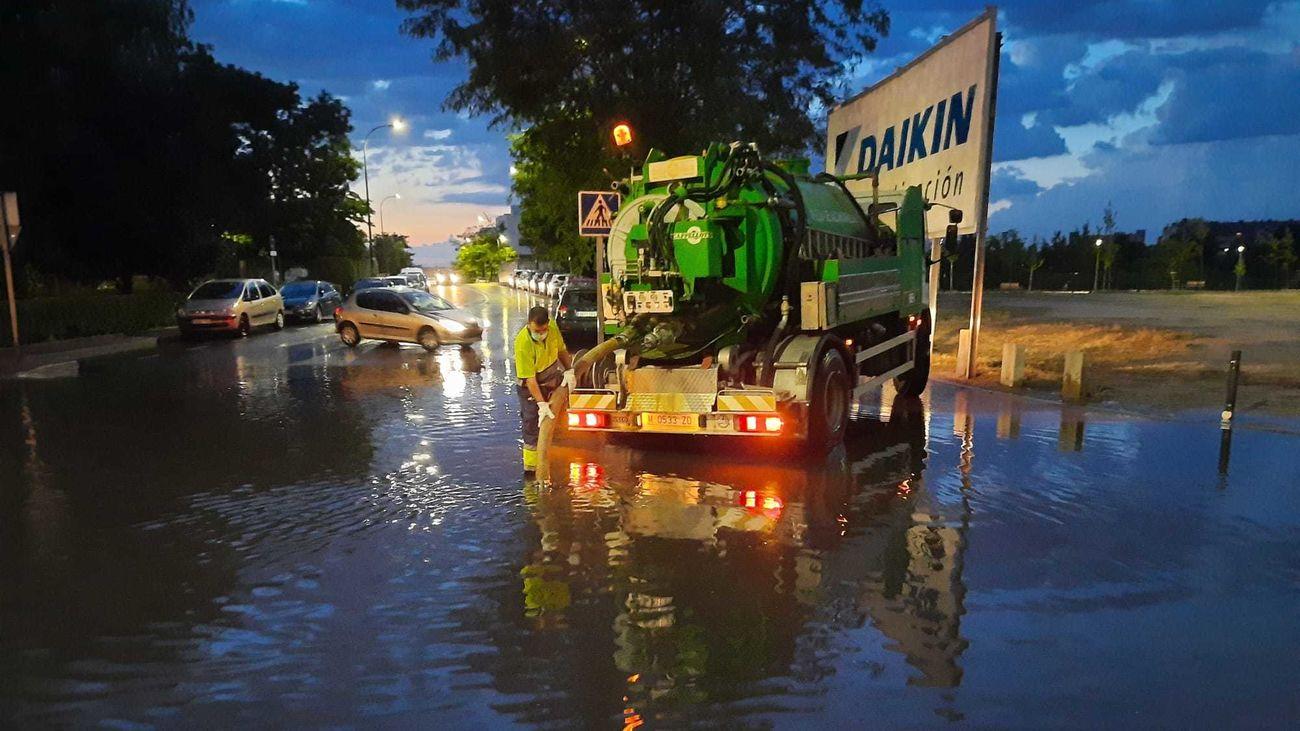 Operarios municipales de Móstoles achican agua en una calle tras la tormenta de este miércoles