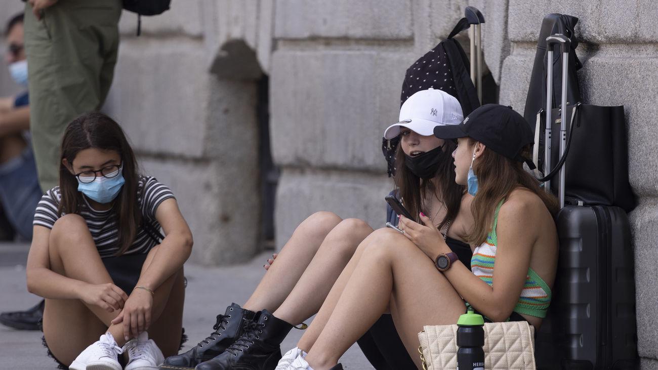 Tres jóvenes turistas con maletas sentadas en el suelo de una calle de Madrid