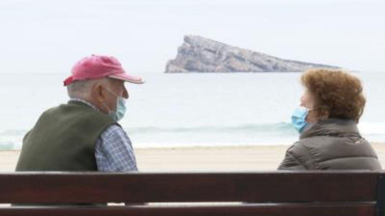 Dos personas sentadas frente a la playa alicantina de Benidorm