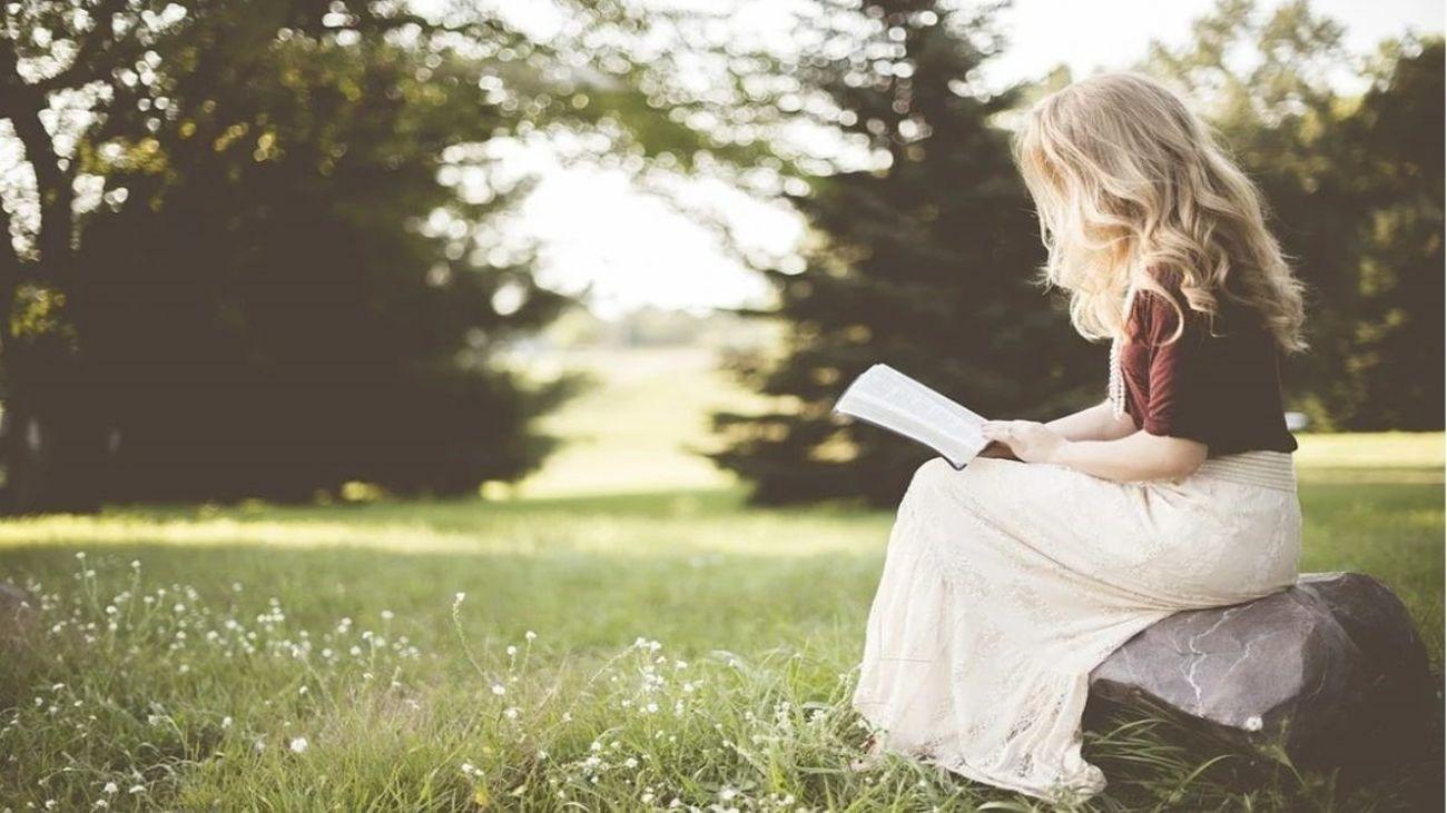 Una joven lee en mitad del campo