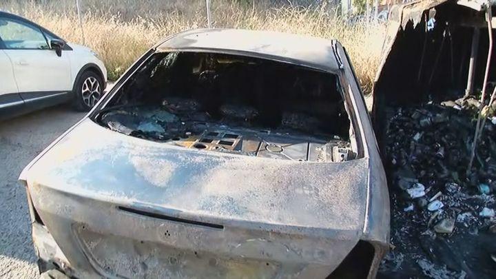 Un coche queda calcinado tras la quema de un contenedor cercano en Hortaleza