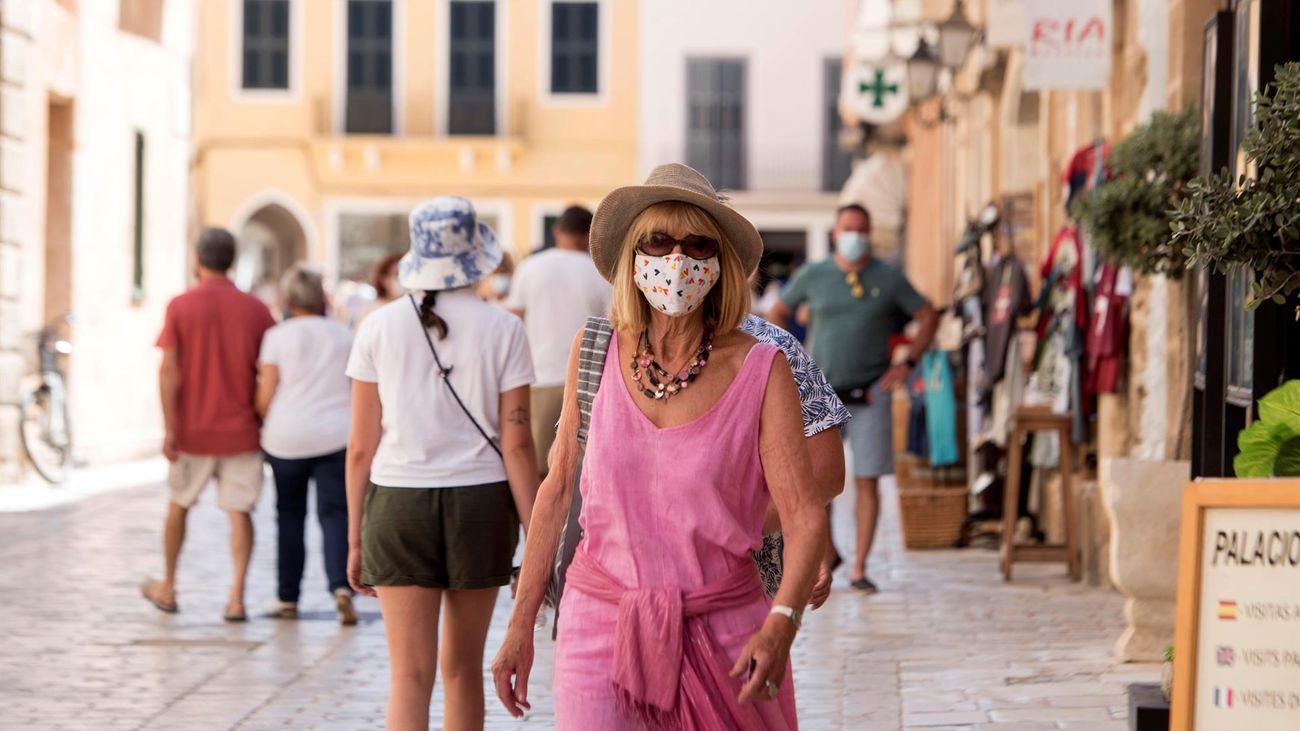 Varias personas con mascarilla en la calle