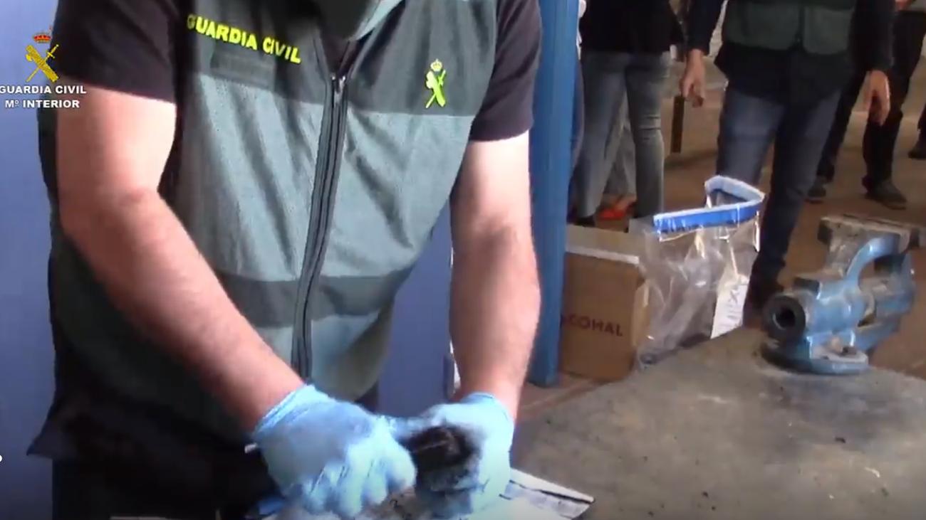 Un agente de la Guardia Civil extrae muestras de una pieza de automóvil para ser  analizadas