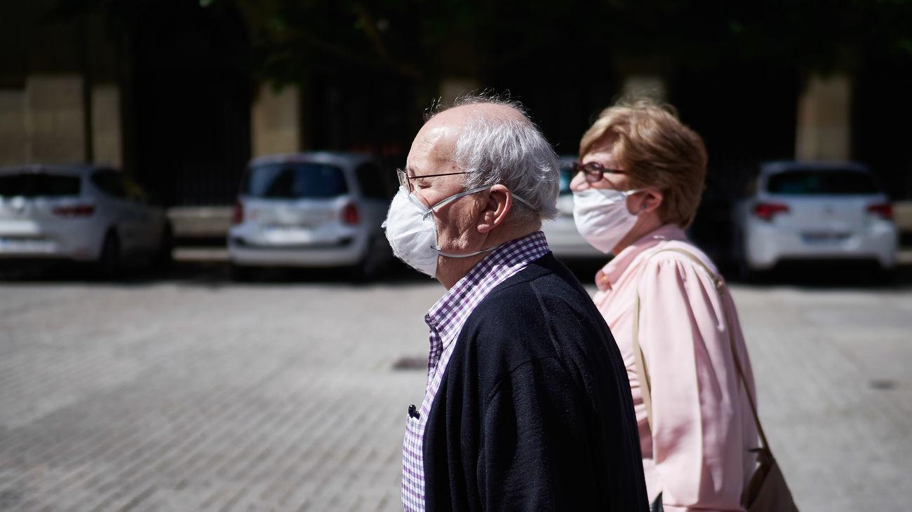 Dos personas mayores caminan por la calle