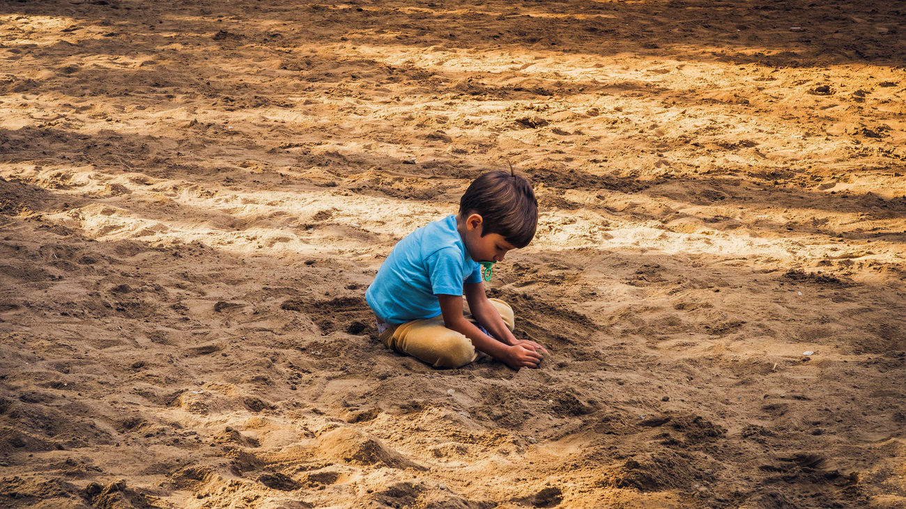 Un niño juega en la arena de un parque
