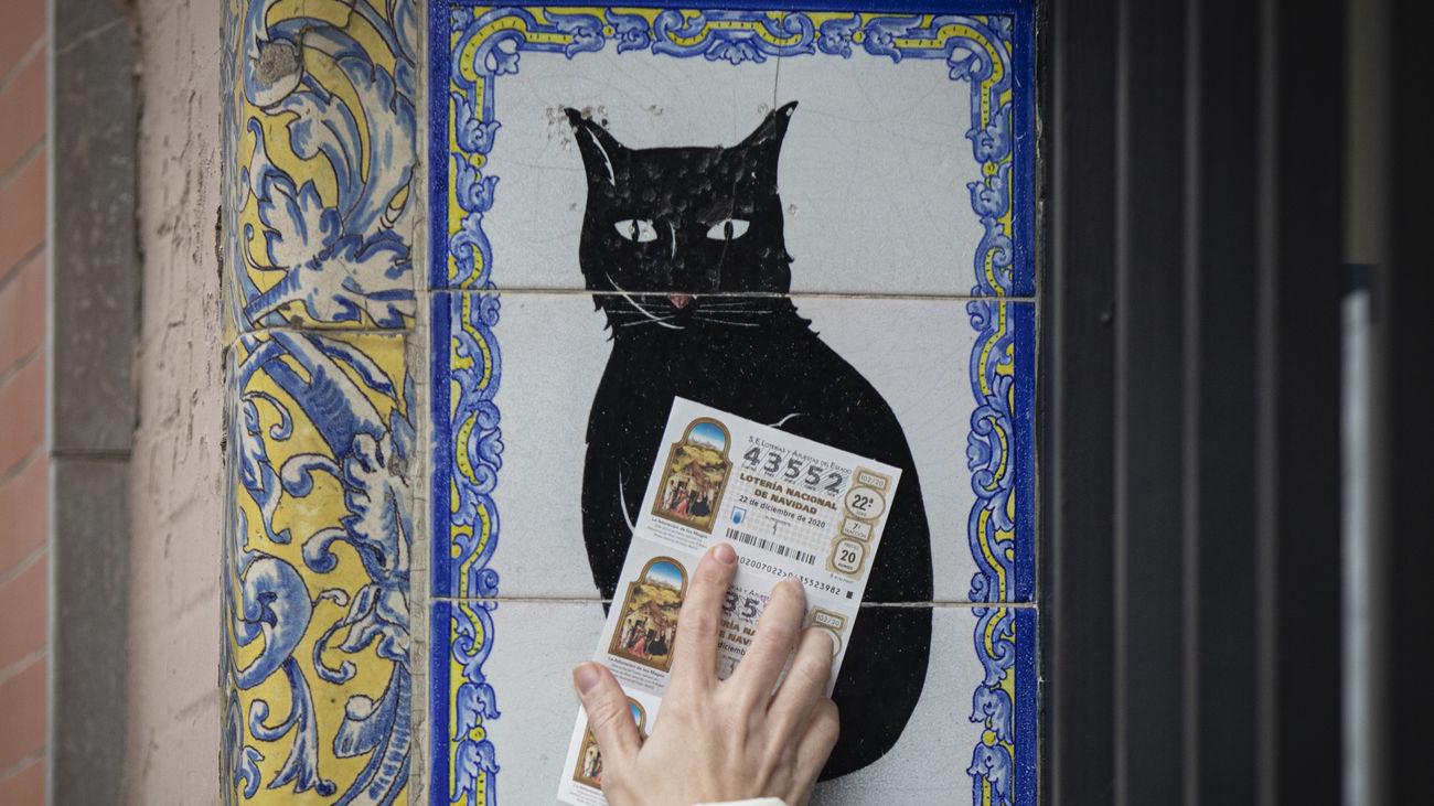 Una persona pasa un décimo de Lotería por azulejo de 'El gato negro'