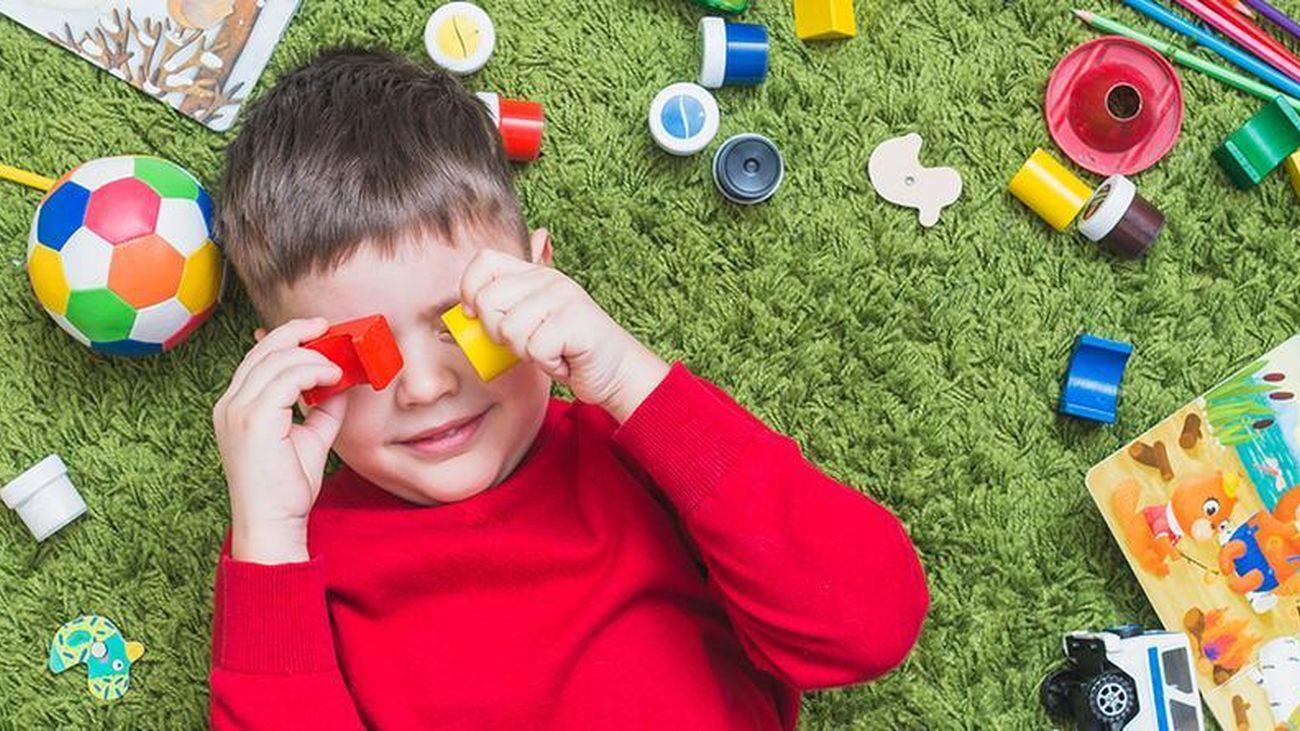 Un niño juega tumbado en el suelo