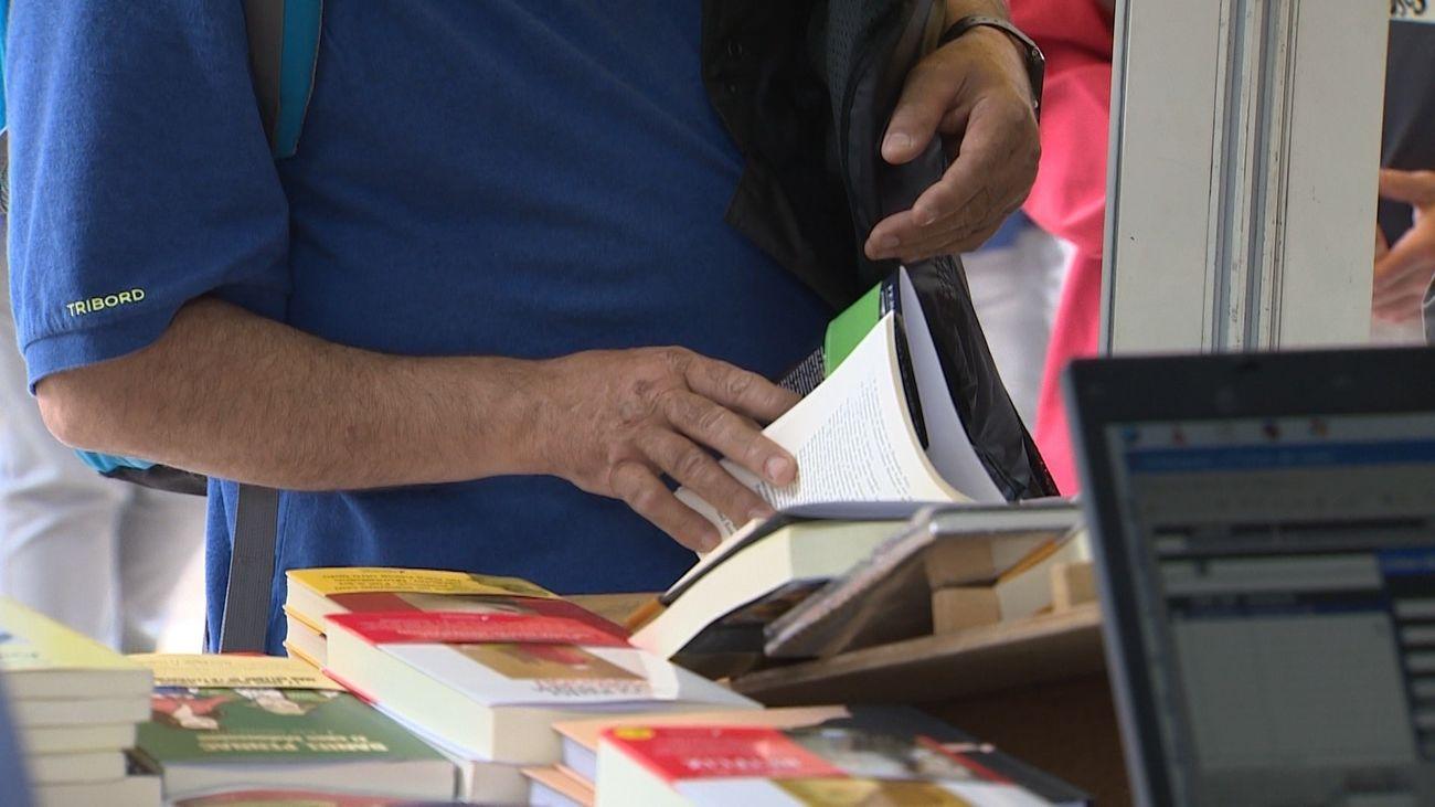 Un hombre mira un libro en la Feria del Libro de Madrid